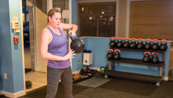 woman exercising with kettlebell in gym