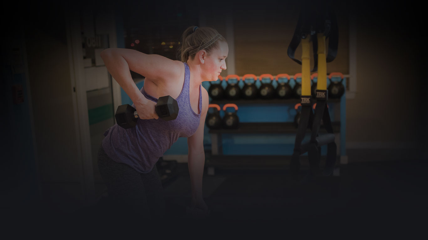woman exercising with dumbbell in hand