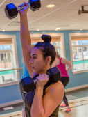 woman exercising with dumbbell over head in gym