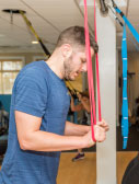 man exercising with resistence bands in gym