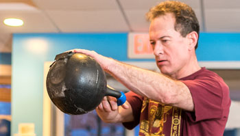 man exercising with kettlebell in gym