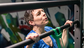 woman exercising with pulll up in gym